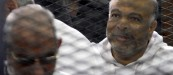El-Katatni sits in the defendant's cage With Badie during their trial in Cairo