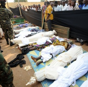 People stand near bodies found lying in a mosque and in its surrounding streets in the Central African capital Bangui on December 5, 2013, after overnight violence. AFP reporters counted 54 corpses in a mosque in the PK5 area of the capital and another 25 lining surrounding streets, all of them with bullet or machete wounds as the United Nations authorised French-backed military intervention in the imploding Central African Republic.  AFP PHOTO/ SIA KAMBOU