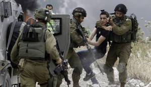 Israeli soldiers detain a Palestinian protester following a demonstration against the expropriation of Palestinian land by Israel in the West Bank town of Tulkarem on May 31, 2014.